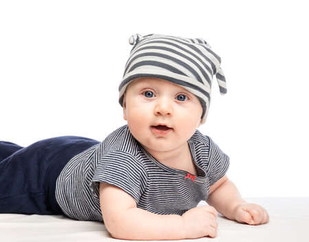 Portrait of cute 5-months baby boy wearing striped cap and shirt lying down on a blanket looking at camera. Studio shot with isolated background