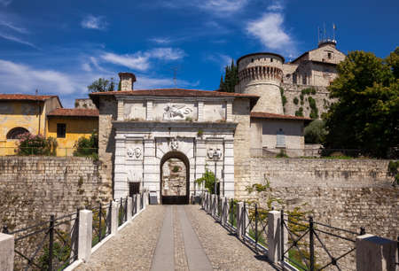 Main entrance to Castle of Brescia (Castello di Brescia) or Falcon of Italy (Falcone d'Italia) in Brescia, Lombardy, Northern Italy. Footbridge over the moat leads to the white marble arched gate, decorated with Venetian winged lion