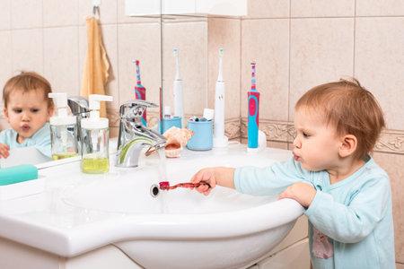 Baby girl wearing blue sleepers learning to brushing teeth in a bathroom Standard-Bild