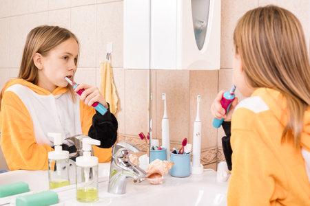 Tween girl wearing orange pyjamas brushes her teeth with electric toothbrush in a bathroom