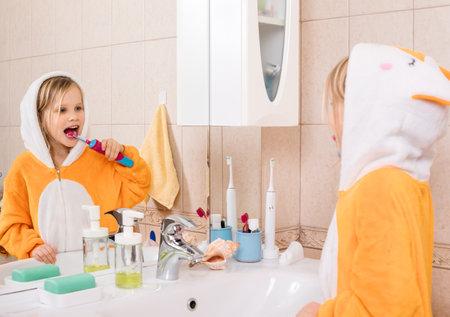 Five year old girl wearing orange pyjamas brushes her teeth with electric toothbrush in a bathroom