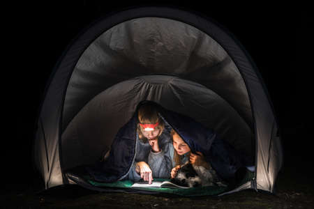 Preteen girls laying in a camping tent wrapped in a sleeping bag reading a book with flashlight at night during summer holidays Standard-Bild