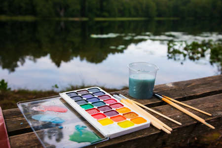 Close-up of watercolor setup with aquarelle palette paintbrushes and water jar lay on a wooden bench by a forest lake - plein air scetching concept