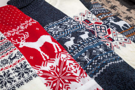 Various warm seasonal Christmas jumpers aka Ugly sweaters with deer and snowflake ornament laid folded