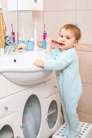 Baby girl wearing blue blanket sleeper learning to brush teeth in a bathroom Standard-Bild