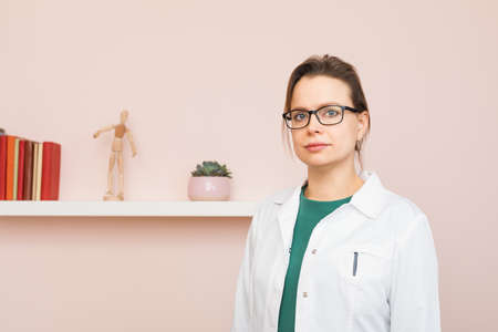 Portrait of confident young female doctor wearing white coat and glasses standing in her home office looking at camera Standard-Bild