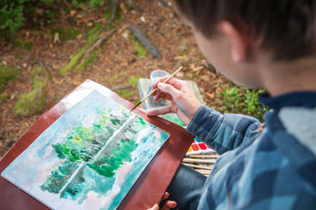 Teenager boy sitting by forest lake painting landscape with watercolor - plein air painting concept