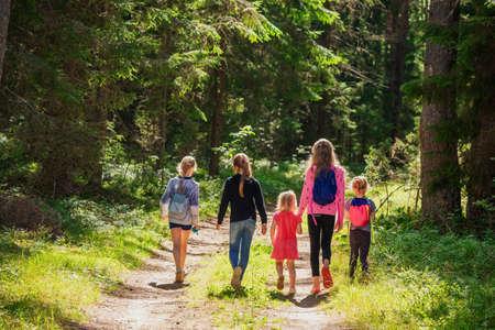 Little girls walking along a trail through summer forest enjoying warm sunny day- summer holidays concept