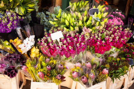 Various flower bouquets in baskets with price tags for sale at a street market in England