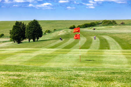 Green field and red flagstick of a golf course,  Southern England, UK. Golf players are seen in background Standard-Bild