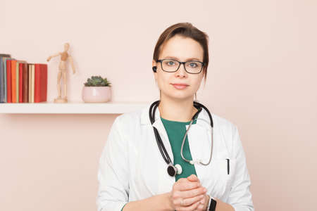 Portrait of confident young female doctor wearing white coat with stethoscope and earpiece standing in front of a camera at her home office performing online consultation