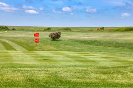 Green field and red flagstick of a golf course,  Southern England, UK Standard-Bild