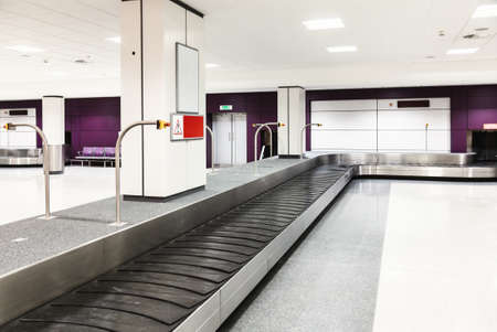 Airport baggage reclaim area with empty baggage pickup carousel