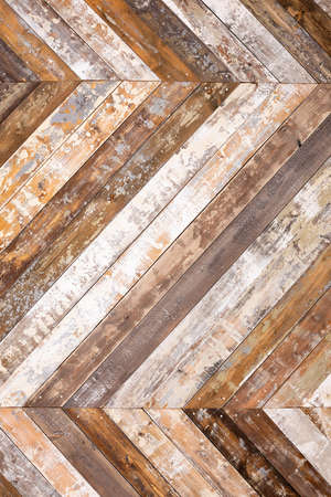 Wall decorated by wooden planks with peeled paint folded herringbone textured background