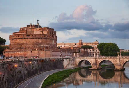 Evening view of Tiber embankment with the Mausoleum of Hadrian or Castel SantAngelo circular 2nd-century castle and Ponte Sant Angelo ancient pedestrian bridge in Rome, Italy Editorial