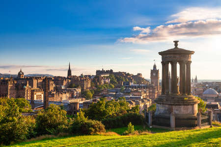 Edinburgh cityscape as viewed from the Calton Hill with the Dugald Stewart Monument in foreground in the evening sun