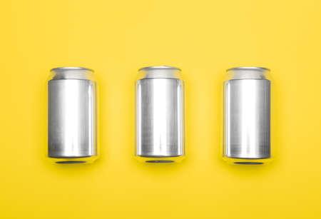 Three 330 ml aluminum beverage drink soda can temlpates on yellow background 版權商用圖片