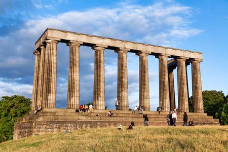 Edinburgh, UK - Aug 9, 2012: Tourists enjoy sunny evening at the National Monument of Scotland on the Calton Hill