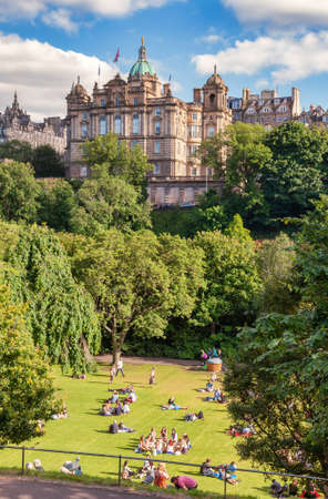 Edinburgh, UK - Aug 9, 2012: Locals and tourists enjoy warm sunny summer day relaxing and picnicking at the Princes Street Gardens, a famous public park in the city center 新聞圖片