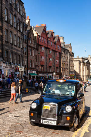 Edinburgh, UK - Aug 9, 2012: Black Cab waiting for client at Royal Mile, a popular tourist attraction and the busiest tourist street in the Old Town