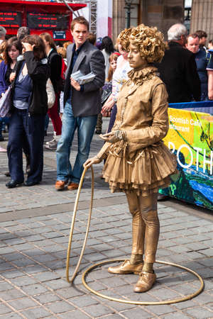 Edinburgh, UK - Aug 9, 2012: Street performer poses as a living statue during the Fringe Festival, the worlds largest annual arts festival