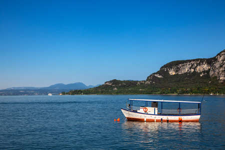 Pleasure boat moored near resort town on the eastern shore of Lake Garda in Northern Italy. Lake Garda is the largest lake in Italy and a popular holiday location on the edge of the Dolomites