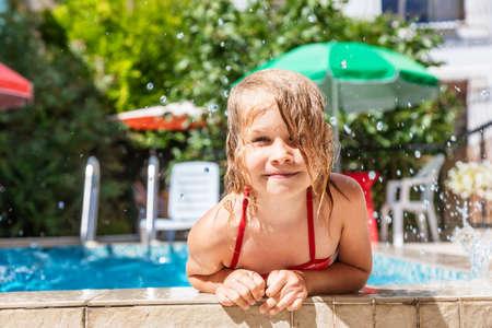 Happy little girl having fun playing in outdoor pool splashing water during summer holidays 版權商用圖片