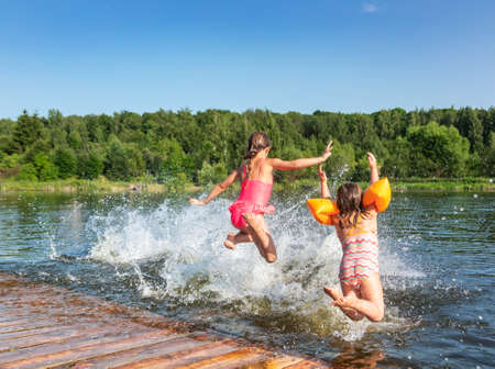 Happy little girls having fun playing in a lake jumping into water during summer holidays 版權商用圖片