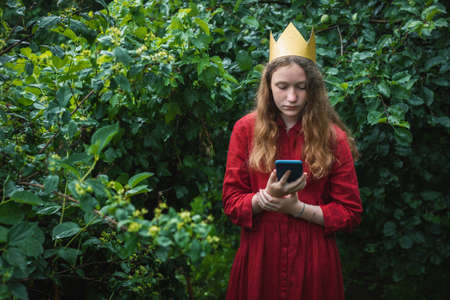 Preteen girl wearing red dress and paper crown standing in wet garden using phone
