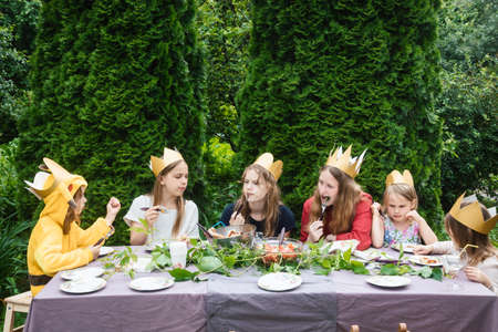 Children wearng paper crowns sitting by  decorated table eating grilled sausages celebrating birthday party in a green garden