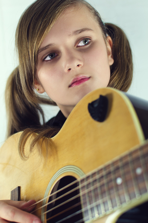 Girl with a guitar in plaid shirt
