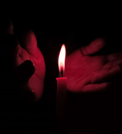 Hands supporting flame of candle at night.