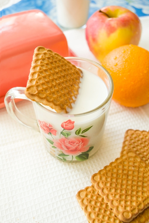 square cookie soaked in a mug of milk