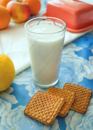 glass of milk with cookies on blue background