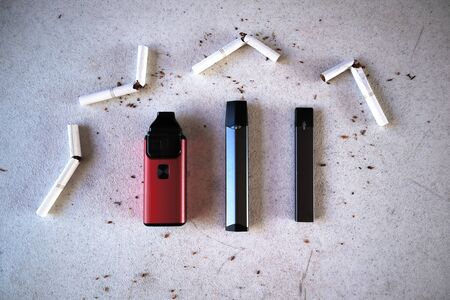 Different vape devices electronic cigarettes as smoking alternatives with broken cigarettes and scattered tobacco on white textured background