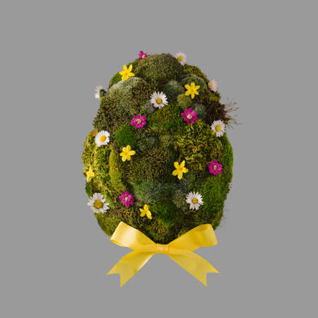 Easter egg shape made of green moss and colorful spring flowers Stock fotó