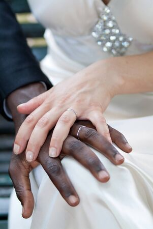 spouses: White womans hand on black mans hand - spouses