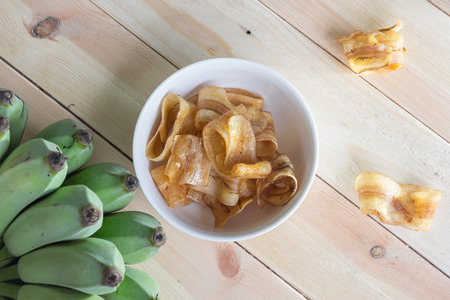 platanos fritos: patatas fritas de plátano dulces en un recipiente con el fondo de madera.