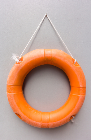 Close-up View of orange lifebuoy hanging on wall Editorial