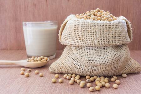 soymilk: Soybean in hemp sack bag with soymilk in glass setup on wooden table.
