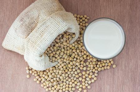 leche de soya: Soybean in hemp sack bag with soymilk in glass setup on wooden table.