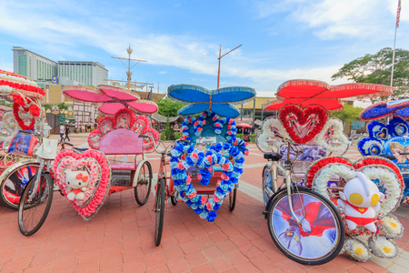 rickshaw: MALACCA, MALAYSIA - AUGUST 12, 2016: The decorated trishaw parking in a Famosa Castle in Malacca,tourists and local people can seen around the Famosa Castle in Malacca