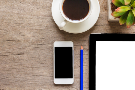 Top view and close up of old wooden desktop with tablet, smartphone, coffee cup, decorative plant and pencil.