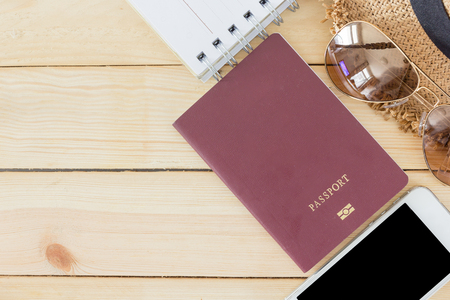 noted: Preparation for Traveling concept, passport, smartphone, sunglasses, noted book, hat on a wooden background with copy space.