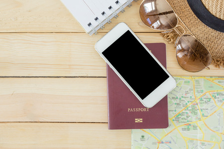 noted: Preparation for Traveling concept, passport, smartphone, sunglasses, noted book, map on a wooden background with copy space. Stock Photo