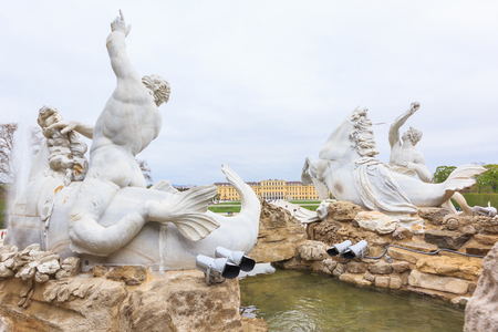 schoenbrunn: Neptune fountain (1780) and the magnificent Schloss Schonbrunn Palace (1713) built for the Habsburg Dynasty in the beautiful city of Vienna, Austria. Editorial