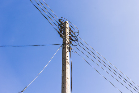 against the current: electrical post by the road against blue sky