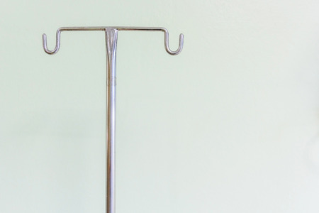 Empty intravenous pole hanger for serum, blood and pharmaceutical bags in brightly lit hospital room at treatment end.