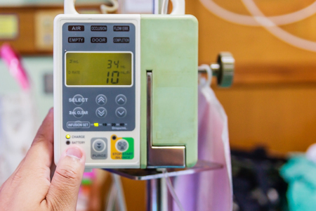 Automatic infusion pump and IV hanging on pole in patient room Stock Photo
