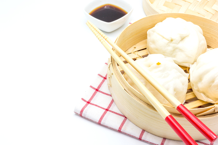 Steamed pork buns (chinese dim sum) in bamboo basket, serve with chopsticks and napkin on a white background, Top view with copy space and text. Stock Photo